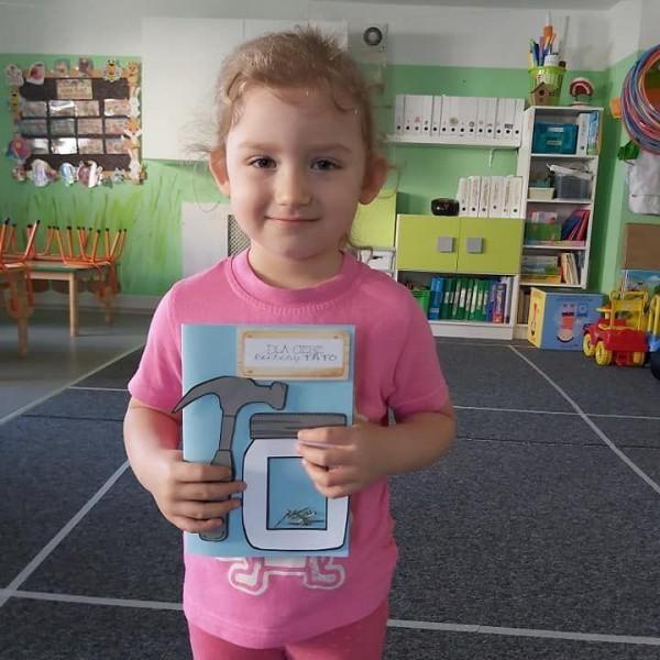 dziecko stojące przed aparatem z zeszytem 9