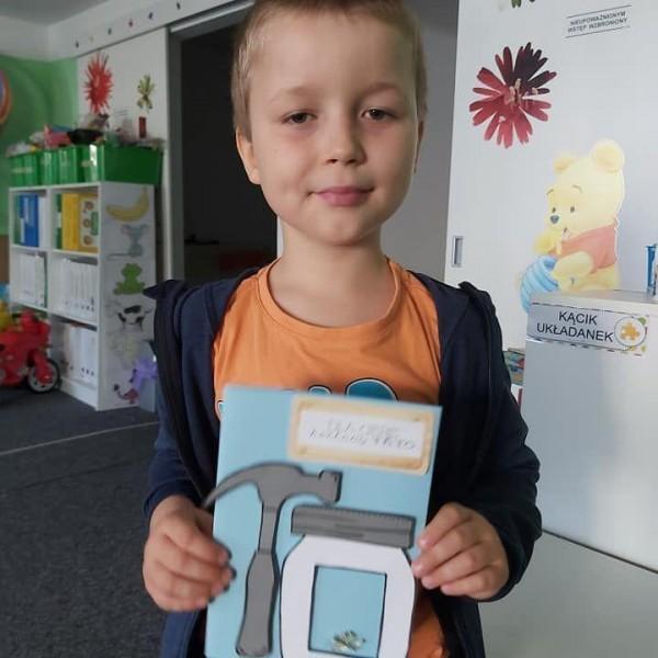 dziecko stojące przed aparatem z zeszytem 8
