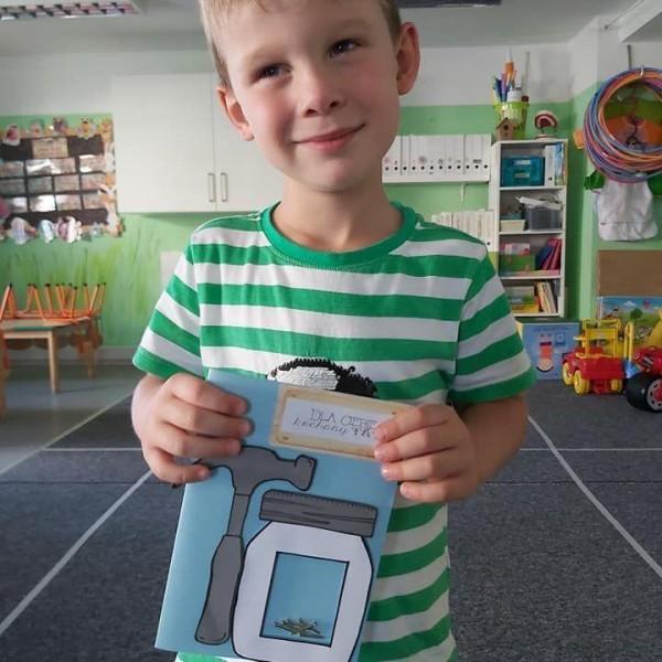 dziecko stojące przed aparatem z zeszytem 4