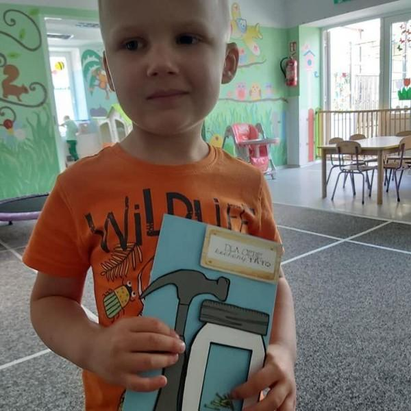 dziecko stojące przed aparatem z zeszytem 3