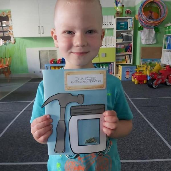 dziecko stojące przed aparatem z zeszytem 2