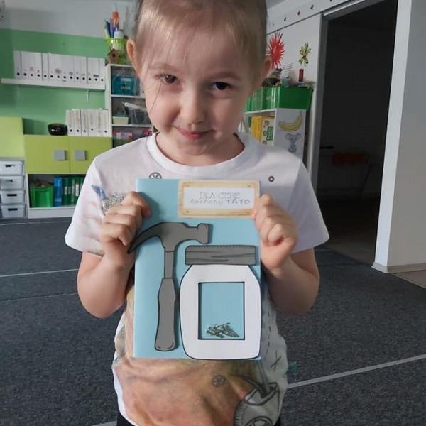 dziecko stojące przed aparatem z zeszytem 1